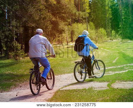 Active Senior Couple Riding Bikes In Nature, Active Retirement