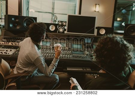 Back View Of Sound Producers Looking At Blank Monitor At Recording Studio