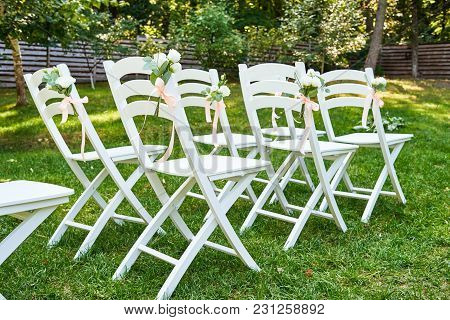 White Wedding Chairs With Fresh Flowers On Each Side Of Archway Outroods, Copy Space. Empty Wooden C