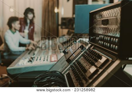 Close-up Shot Of Sound Amplifiers At Recording Studio With Blurred Producers Behind