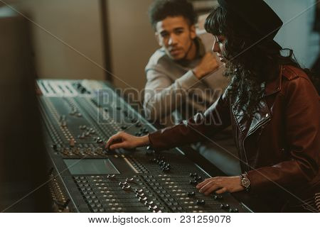 Sound Producers Working With Graphic Equalizer At Recording Studio