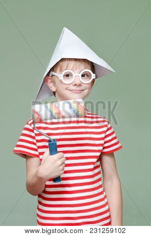 Boy In A Paper Hat And Glasses. Portrait. Roller For Painting