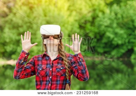 Girl In The Helmet Of Virtual Reality Against The Background Of Nature. Hands Up