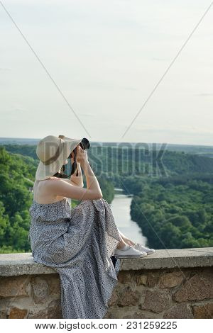 The Girl In A Sundress And A Hat With A Camera. Hill, Green Forest And River Below