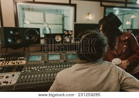 Sound Producers Looking At Singer At Recording Studio