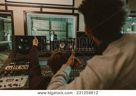 Sound Producers Showing Thumbs Up To Singer At Recording Studio