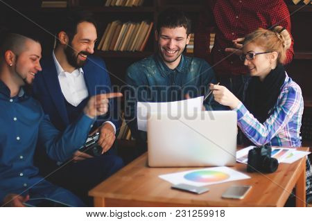 Team Of Copywriters Discussing A New Advertising Project In Modern Office