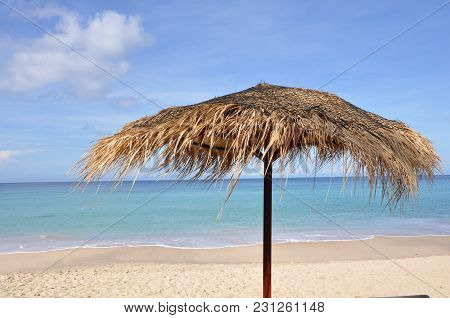 A Beautiful  Straw Umbrella On The Beach At Daytime On The Empty Beach