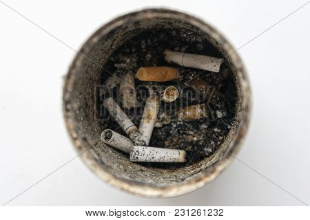 Old Tin Box With Cigarette Butts Inside. Photo On A White Background...