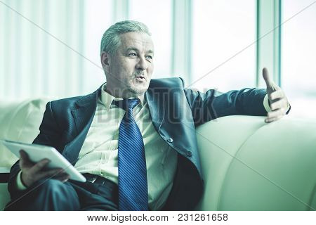 Experienced Businessman With Digital Tablet Sitting On The Sofa In The Private Office.