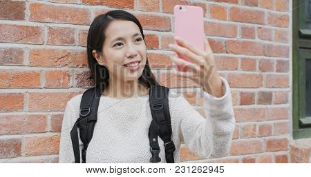 Woman talking on cellphone over red brick wall