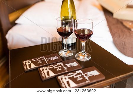 Two Glasses Are Filled With Red Wine. Near The Wineglasses Stand A Wine Bottle And A Few Chocolates