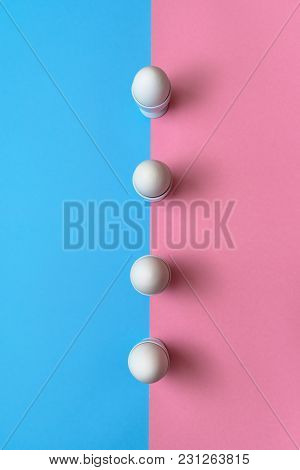 White Eggs Standing On Egg Cup On Blue And Pink Pastel Background, Copy Space. Row Of Boiled Eggs In