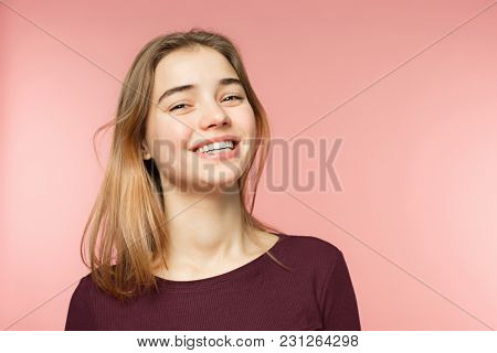 Woman Smiling With Perfect Smile And White Teeth On The Pink Studio Background And Looking At Camera