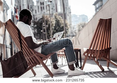Reading The Latest News. African American Young Man In Casual Sitting On A Wooden Chair And Concentr
