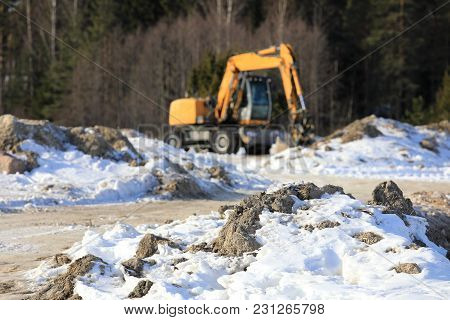 Construction Site In Winter, With Yellow Mid-size Hydraulic Excavator Defocused On The Background. S