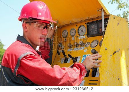 Oil And Gas Well Drilling Worker Operates Drilling Rig Machinery.