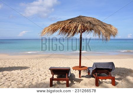 A Beautiful  Straw Umbrella With Sunbeds  On The Beach At Daytime On The Empty Beach