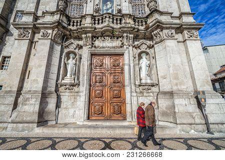 Porto, Portugal - December 8, 2016: Couple Passes In Front Of Entrance Door Of Carmo Church In Porto