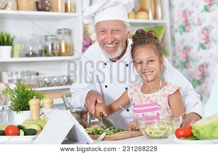 Senior Man In Chefs Uniform Preparing Dinner With His Granddaughter