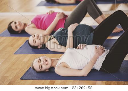 Cheerful Pregnant Women In Yoga Class Are Lying On Mats In A Fitness Studio.