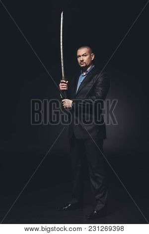 Serious Man In Suit With Japanese Katana Sword On Black