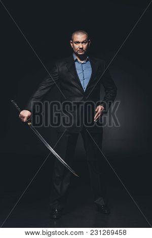 Modern Samurai In Formal Suit With Katana Sword On Black