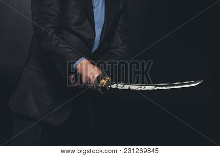 Cropped Shot Of Man In Suit Holding Japanese Katana Sword On Black