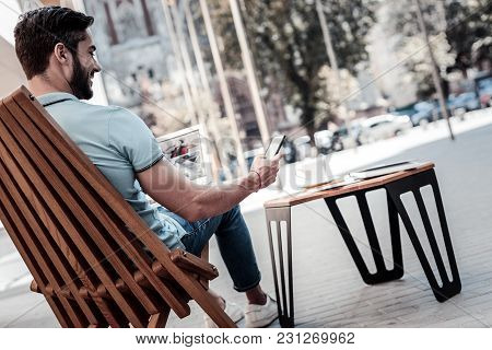 Getting Updated. Turned Back Millennial Guy Sitting In A Wooden Chair And Beaming While Browsing Soc