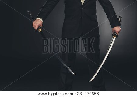 Cropped Shot Of Man In Suit With Dual Katana Swords On Dark Background