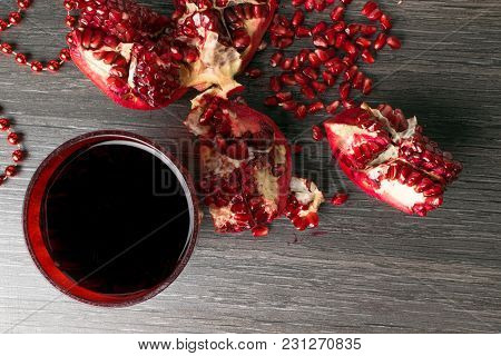 Pomegranate Composition With Red Beads, Pomegranate, Juce In Glass In Dark Bakground