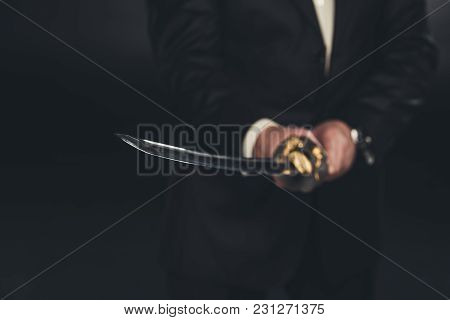 Cropped Shot Of Man In Suit With Katana Sword On Dark Background