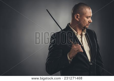 Thoughtful Man In Suit With Katana Sword On Black