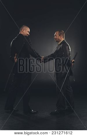 Side View Of Yakuza Members Shaking Hands With Katanas Behind Back Isolated On Black