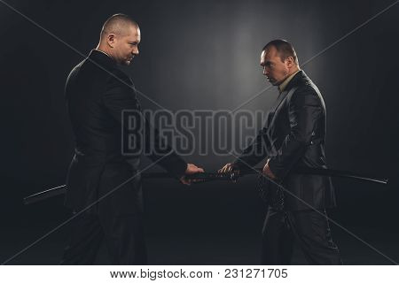 Side View Of Businessmen Taking Out Katana Swords For Fight Isolated On Black
