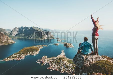 Couple Travelers Traveling Together On Top Cliff Reinebringen Mountain In Norway Man And Woman Famil