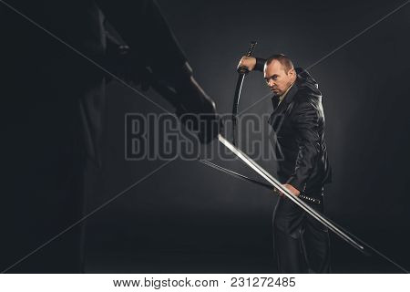 Mature Modern Samurai In Suit Ready To Fight On Black
