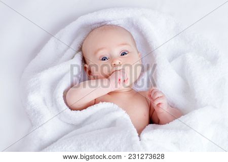 Sweet baby in a white towel after bath. Healthcare, pediatrics.