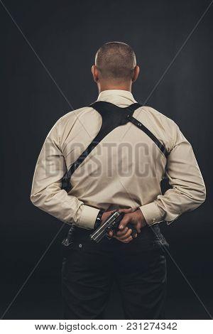 Back View Of Mafia Member In Shirt Holding Gun Behind Back