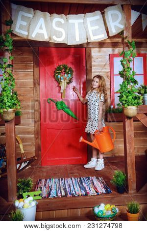 Pretty child girl with watering can stands on the porch of a wooden house. Rural style decoration. Household chores. Easter holidays.