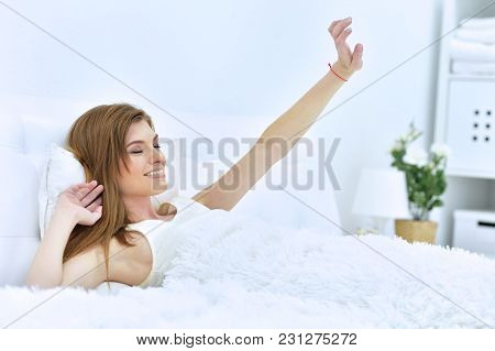 Young Woman Waking Up In Bed At Home