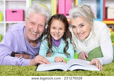 Little Cute Girl With Grandparents  Studying At  Home