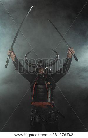 Samurai In Armor With Dual Katana Swords On Dark Background With Smoke