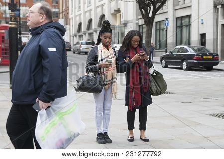 London - September 27, 2016: Young Women  Buried In The Phone, Waiting For The Subway Around Covent