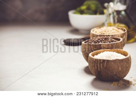 Assortment of different rice in bowls: Rice berry, Brown rice and Risotto rice and cooking ingredients  on grey concrete background. Clean eating