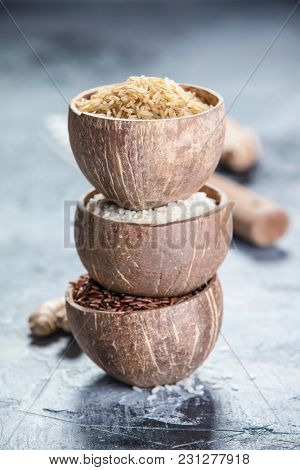 Assortment of different rice in bowls: Rice berry, Brown rice and Risotto rice on grey stone background.
