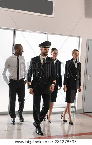 Happy Aviation Personnel Team In Professional Uniform Walking By Airport