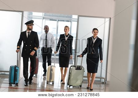 Young Aviation Personnel Team With Suitcases At Airport