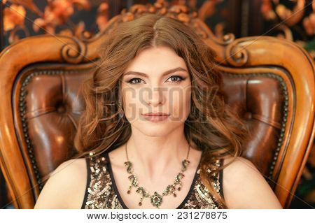 Portrait Of Beautiful Young Woman Sitting In Vintage Chair