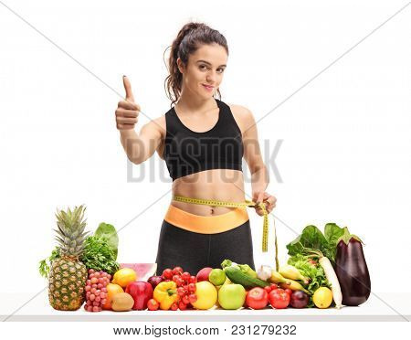 Fitness girl measuring her waist with a measuring tape and making a thumb up sign behind a table with fruit and vegetables isolated on white background